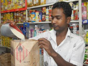 A retailer measures rice into a bag at a retail outlet
