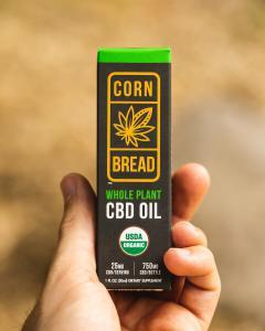A customers holds a package of Cornbread Hemp's USDA certified organic Whole Flower CBD Oil.