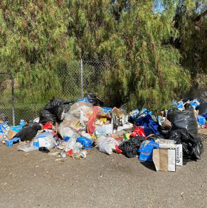 A large amount of trash is located next to a fence.