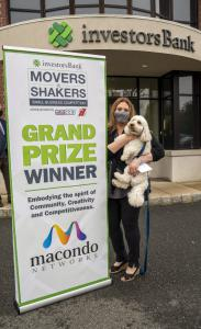 Jennifer Frey, managing partner of Macondo Networks, is holding Dash, a golden doodle dog, which is the company mascot. Frey is standing next a sign that Grand Prize winner, Movers & Shakers competition.