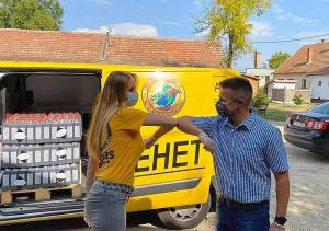 "Keeping the protocols in place, instead of shaking hands, a Volunteer Minister exchanges an ""elbow bump"" with Csökmő Mayor Tibor Nagy who helps unload, divide up and bring supplies to at-risk families."