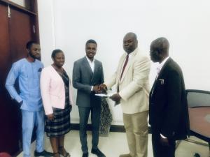 Professor Seth Owusu-Agyei handing documents to Mr Rudolf Schirmer Ampofo-Domfeh,CEO of Augson Global